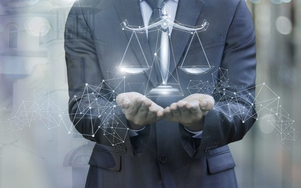 Scales of justice in the hands of a lawyer on blurred background.